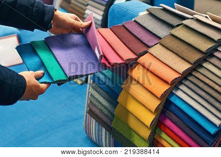 Young woman is making her decision while choosing a color of a fabric from a huge variety in a shop