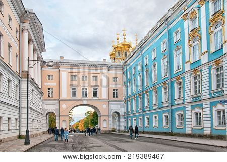 TSARSKOYE SELO, SAINT-PETERSBURG, RUSSIA - OCTOBER 7, 2017: People on the yard of the Imperial Lyceum (left). On the background is the arch between The Lyceum and The Catherine Palace Church Wing