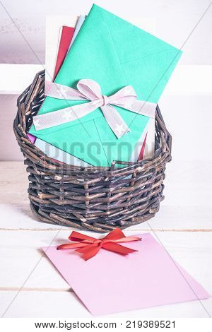 Basket with colorful envelopes and paper note - Wicker basket full of multicolored letters tied together with ribbon and a blank message card with a red bow on a white wooden table.