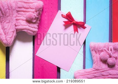 Cute message card and pink bootees - Unwritten pink paper note with red bow surrounded by handmade knitted pink bootees on a multicolored wooden background.