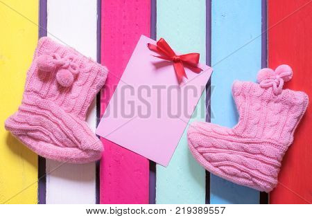 Knitted bootees and a pink paper note - Congratulations on childbirth concept with a message card tied with a red bow surrounded by cute knitted bootees on a colorful wooden background.