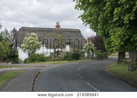 Street view of an old thatched cottage in the pretty village of Foxton Cambridgeshire England UK
