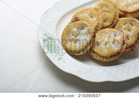 Homemade Christmas Mince pies on a white classic plate over a table with a white tablecloth.