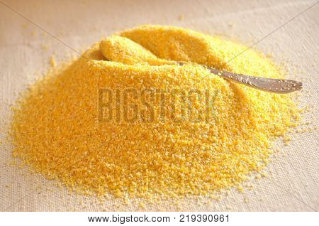 Pile of corn grits on coarse cloth and a spoon on the top of the pile. Close-up image.