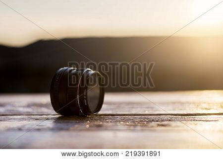 retro 35mm film lens on wooden table with sunshine light