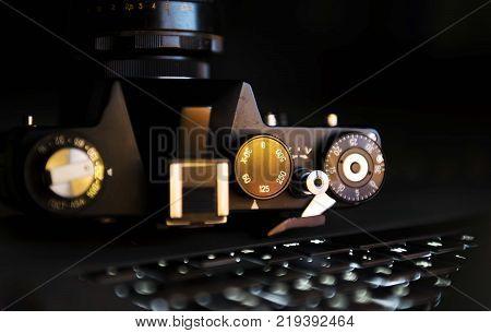 old vintage 35mm film camera standin on laptop