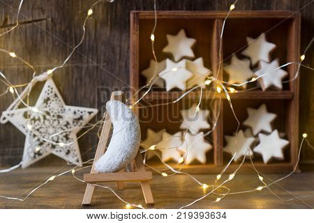 Vanilla crescents and cinnamon stars in the background with a garland, a wooden box and a star. Selective focus.
