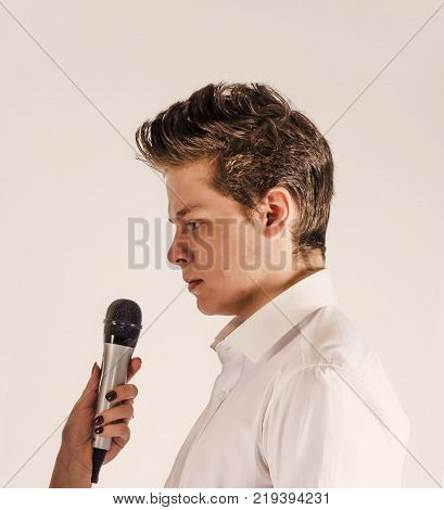 A cute guy looks at the microphone in front of him. Close-up. White background.