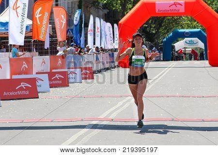 ODESSA UKRAINE - 25 JUN 2017: Excited female runner crossing the finshline of a marathon. Marathon woman at finish. Happy marathon runner finish line.
