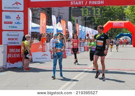 ODESSA UKRAINE - 25 JUN 2017: Excited female runner crossing the finshline of a marathon with kid. Marathon runners woman and man at finish. Happy marathon runner finish line.