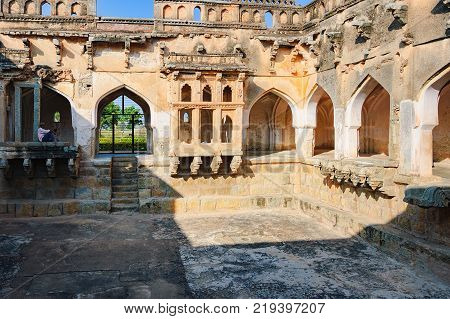 Hampi, India - November 19, 2012: Hindu man is resting among the ancient ruins of Queen's Bath that are located in the southeast of the Royal Enclosure, Hampi, Karnataka, India.