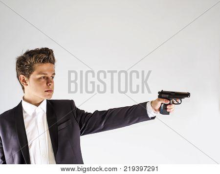 One caucasian spy criminal policeman detective man holding gun portrait silhouette in studio isolated white background