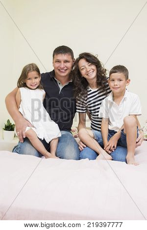 Family Ideas. Happy caucasian Family of Two Parent and Two Kids Sitting Together Embraced.Vertical Image