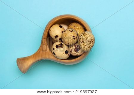 A photo from above of small uncooked quail eggs in wooden mug on the blue table. An overhead photo of quail eggs Easter rustic background
