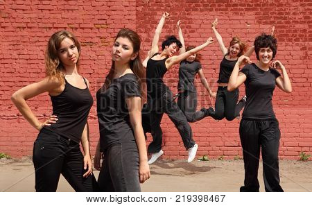 Collage with six girls (four models) in same black clothes jumping on background of brick wall