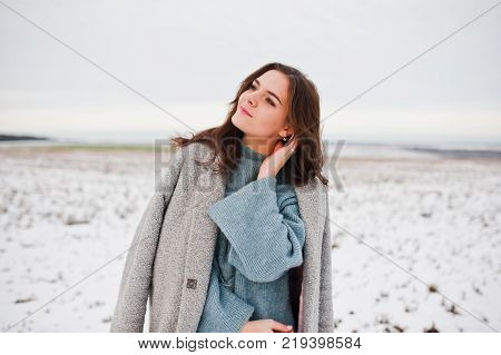 Gentle Girl In Gray Coat And Hat Against Snow Landscape.