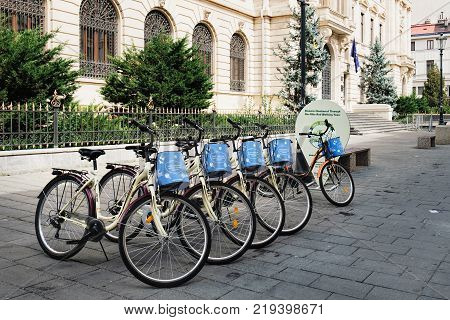 Bucharest, Romania - September 9, 2017: City bike stand with row of bicycles for rent at the historical center Lipscani Street in Bucharest, Romania.