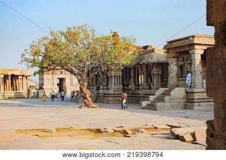 Hampi, India - November 20, 2012: Unidentified Indian tourists visit to the famous landmark Vitthala Temple in Hampi, Karnataka, India. Ancient ruins of Vijayanagara Empire. UNESCO World Heritage Site