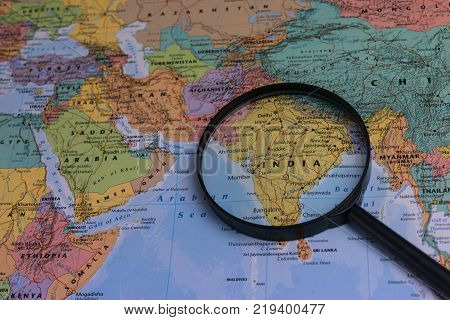 India map through magnifying glass on a world map