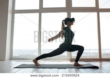 A young beautiful girl in virtual reality glasses makes yoga and aerobics remotely. Modern imaging technology. Classes in single sports remotely.