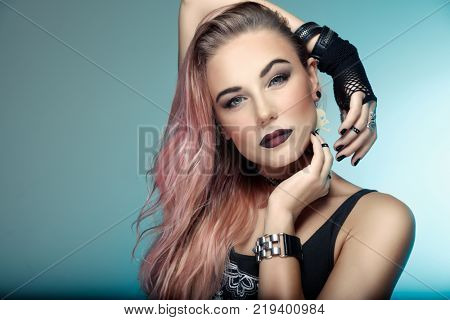 Portrait of a beautiful woman with stylish pink hair over blue background, attractive young girl with dark lips, special style makeup for Gothic party
