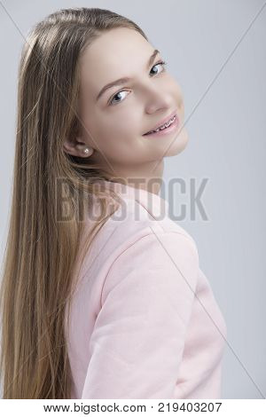 Dental Concepts. Portrait of Happy Teenage Female With Teeth Brackets. Posing Half Turned with Smile Against White.Vertical image