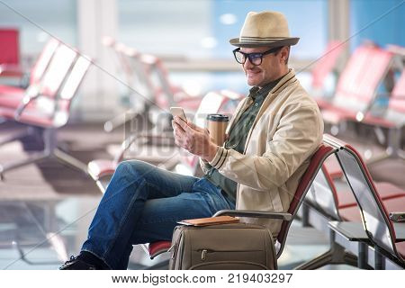 Free wifi. Happy mature man in hat and glasses is sitting at airport lounge and smiling. He is using modern smartphone and drinking fresh espresso