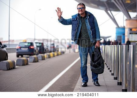 Full length portrait of joyful adult tourist in glasses is raising hand while catching taxi and looking ahead with smile. He is standing near road with backpack. Copy space in the left side