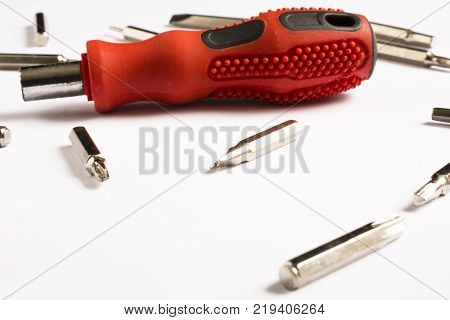 red screwdriver, white background and bits, spare parts