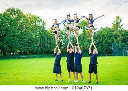 Cheerleading team is practicing on playing field