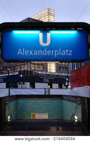 BERLIN, GERMANY - DECEMBER 05: The illuminated blue subway sign Berlin Alexanderplatz in the evening with a video surveillance sign on December 05, 2017 in Berlin.