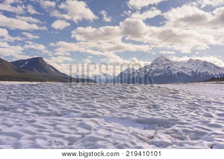 Landscape of the textured ice of Abraham Lake with mountains in the background Alberta Canada.