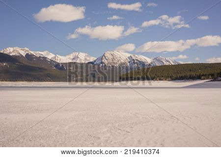 Landscape of snow covered Abraham Lake with mountains in the background.