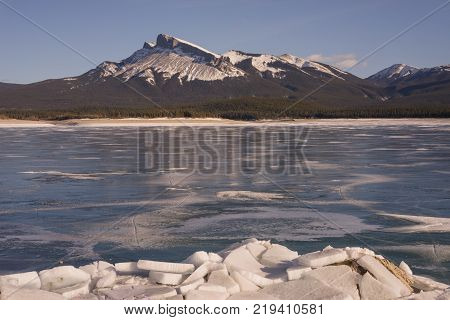 Landscape of icy Abraham Lake with icy chunks in the foreground and mountains in background.