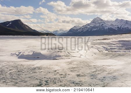 Landscape of broken ice on Abraham Lake with mountains in the background Alberta Canada.