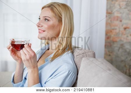 Perfect morning. Side view profile of smiling carefree woman relaxing on daybed in the morning. She is holding cup of tea in hands and looking aside. Copy space in the right side