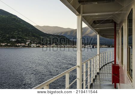 ferry railing and in the distance the port of Sami and its mountains in Kefalonia towards Pisaetos on the island of Ithaka