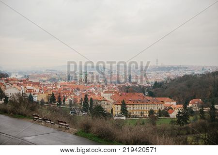 Typical roofs in Prague. Top view - roofs with red tiles in old buildings in Prague. Empty benches stand in a row.