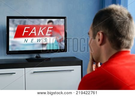 The guy watching the fake news on TV. Corrupt journalism. The false reporting. Deception propaganda and misinformation from television. brainwashed brains of men watching TV.