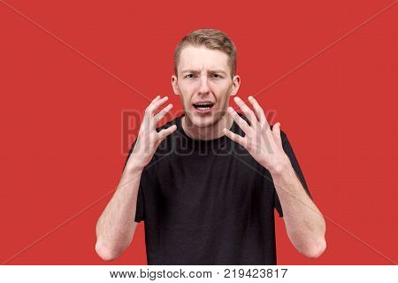 emotional young Caucasian man in a black t-shirt actively gesticulating hands with an indignant dissent expression. The concept of irritability anger indignation