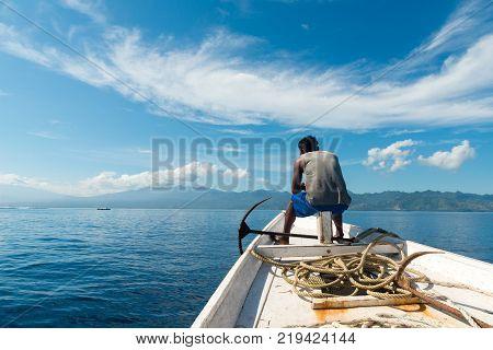 Gili Trawangan, Indonesia - May 6, 2013 - Fisherman sits on his boat during fishing trip in Indonesia
