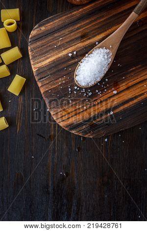 Coarse sea salt in wooden spoon over kitchen board.