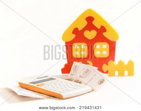 House calculator and money. Estimate calculation. On a white background