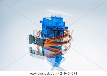 microelectronic servomotor on white background. component for control of robots and radio-controlled toys