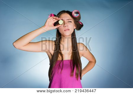 a funny girl holds a piece of cucumber near the eye, to moisturize the skin, on the head of curlers