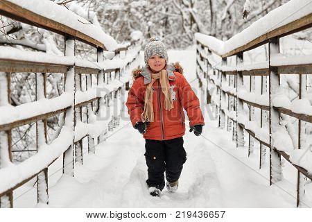 Little Cheerful Boy Runs In Winter On Bridge.