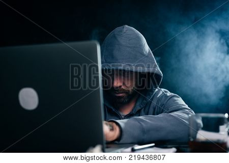 mysterious dangerous man in the hood doing something illegal on the laptop