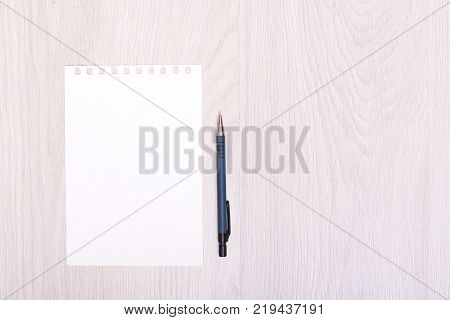 Top view of open spiral blank notebook with pencil on wood desk background. white empty sheet and pencil