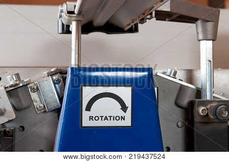 Rotation sign on electric wood jointer in a small workshop.