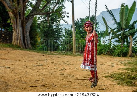 BANDIPUR, NEPAL - OCTOBER 22, 2015 : Nepalese girl in red dress plays on a traditional bamboo swing called linge ping.